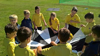 children using parachute for teambuilding purposes