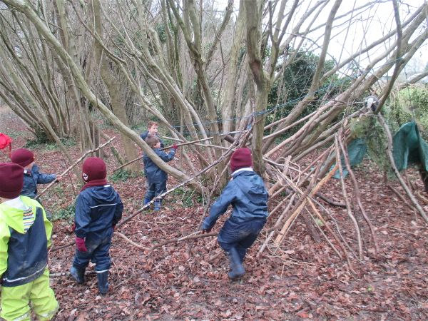 Reception children build a den at forest school